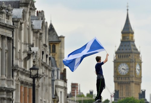 A Scotland soccer fan waves a Scottish saltire flag with Big Ben seen behind in Trafalgar Square in central London